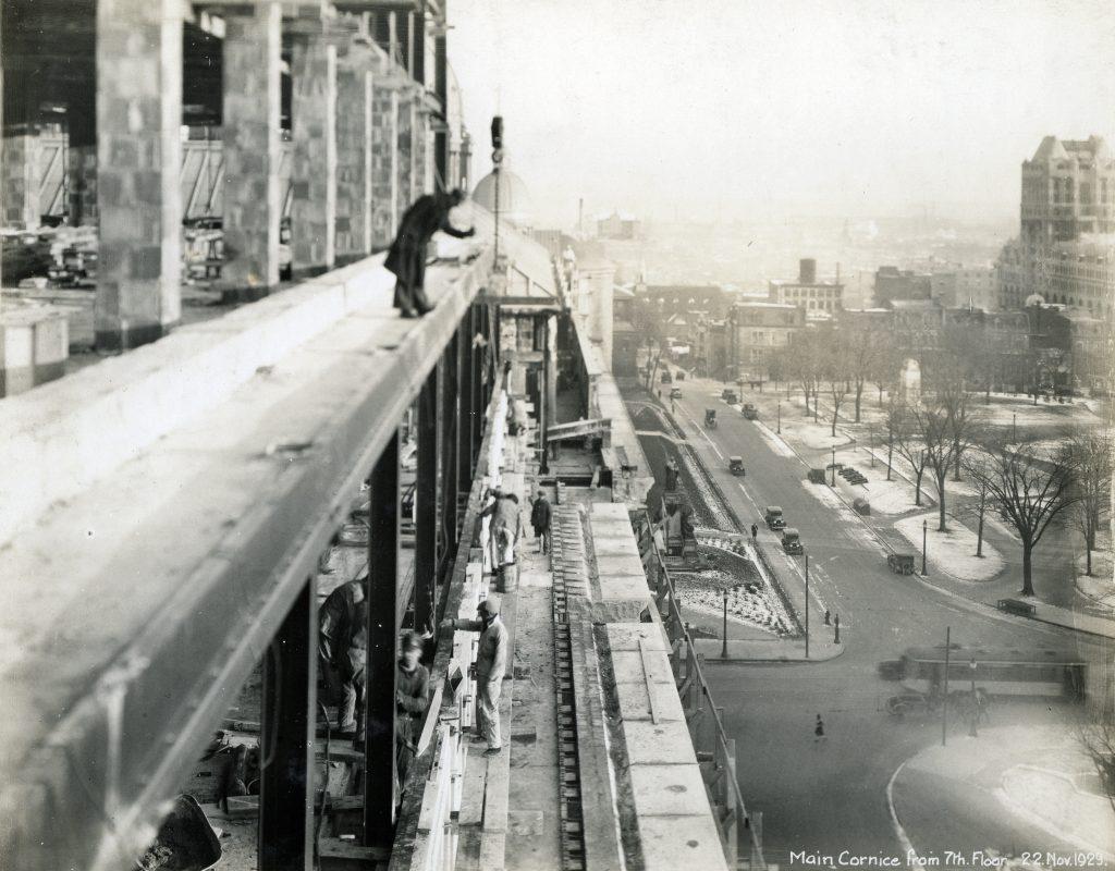 Des ouvriers travaillant sur la corniche principale située au 7e étage, le 22 novembre 1929.